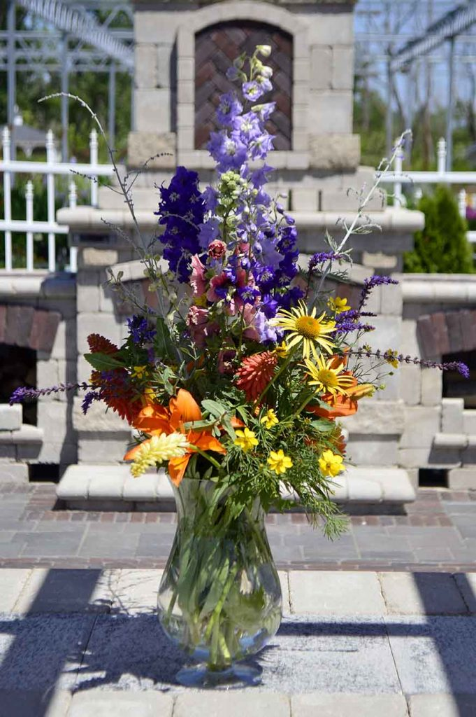 In this arrangement we have: Russian Sage, Coneflower, Asiatic Lily, Delphinium, Hollyhock, Coreopsis, Kniphofia, and Salvia.