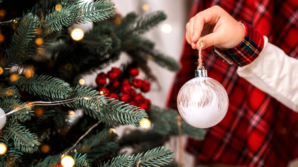 Alsip Real Christmas Tree Care hand of child decorating christmas tree