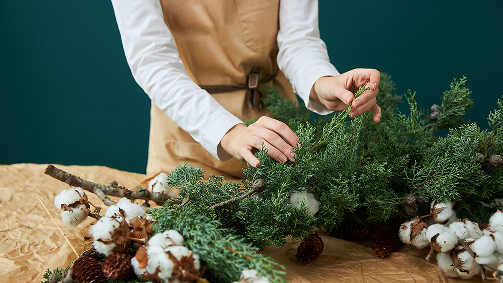 Alsip Nurseries female florist makes a wreath or bouquet of branches of spruce, cones and cotton