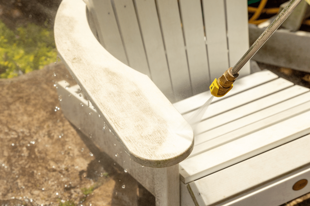 muskoka patio furniture chair being cleaned with a hose in the backyard alsip nurseries