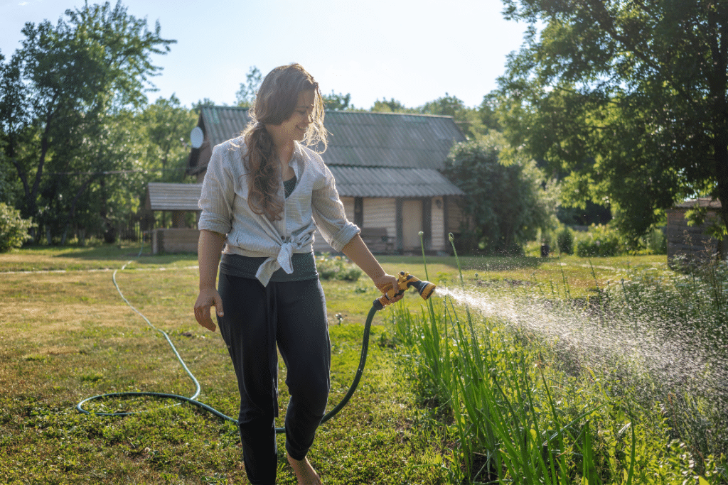 woman watering plants in the backyard on a sunny day alsip nurseries